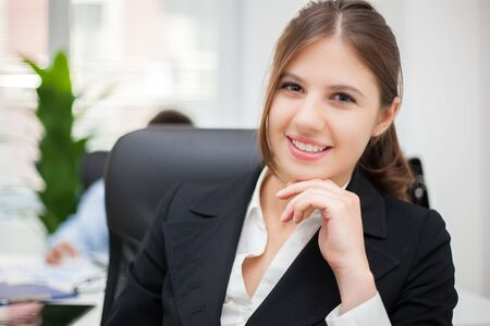 Young secretary at her desk in a modern office Stock Photo