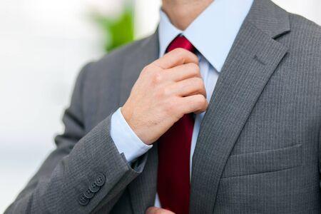 Ritratto di un uomo d'affari regolando la sua cravatta