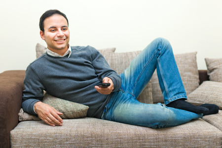 undisturbed: Relaxed man watching TV on his sofa Stock Photo