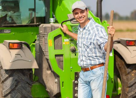 hayfork: Portrait of a smiling farmer holding a pitchfork while working in his field