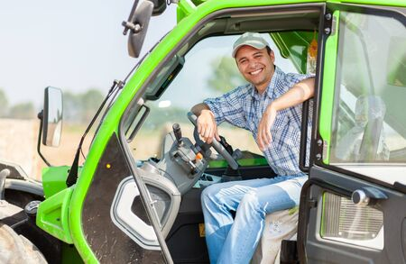 hayfork: Portrait of a smiling farmer in his tractor