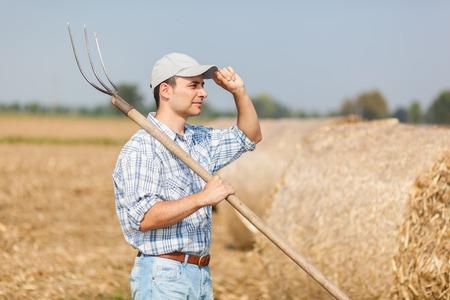 prongs: Farmer holding a pitchfork Stock Photo