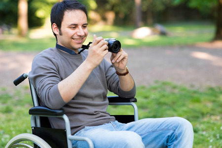 paraplegico: Smiling man using a mirrorless camera Foto de archivo