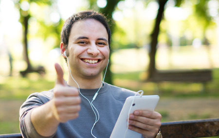 Disabled man listening to music at the park Stock Photo