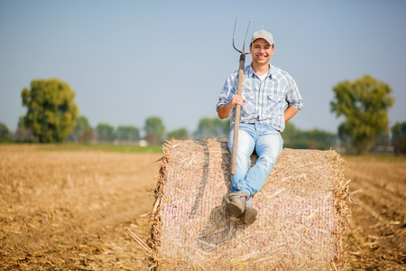 Farmer sitting on a hay bale Stock Photo