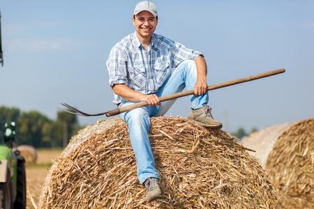hayfork: Portrait of a smiling farmer holding a pitchfork