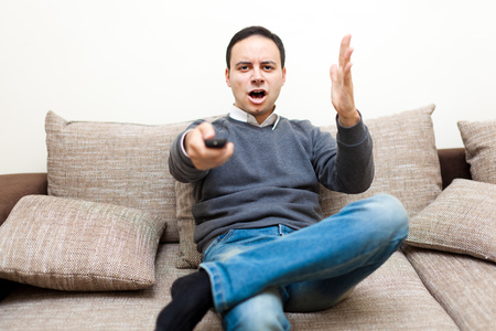 undisturbed: Angry man watching TV on his sofa