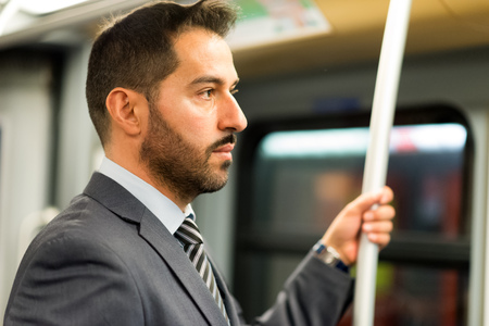 public transport: Businessman hanging to a pole in a train in the subway