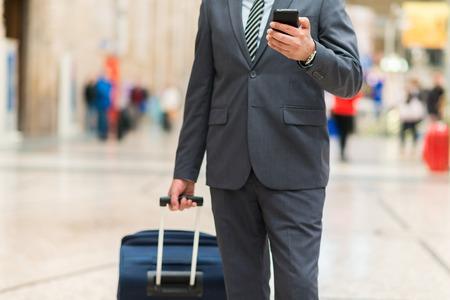Mann , der in einen Bahnhof unter Verwendung seines Smartphone geht
