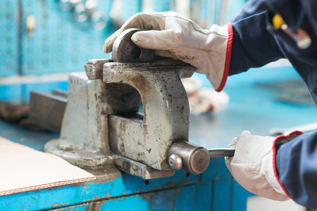 securing: Close-up of a worker securing a metal plate in a vise Stock Photo