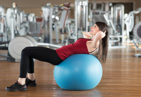 Woman using a ball to work out in a gym