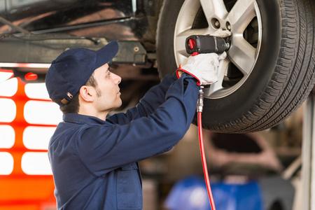 Portrait of a mechanic replacing a wheel