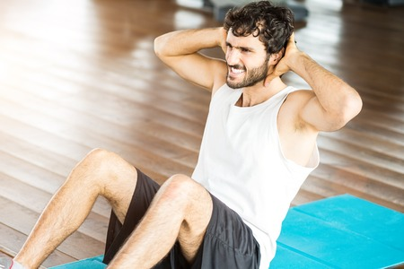 situp: Man working out his abs in a gym