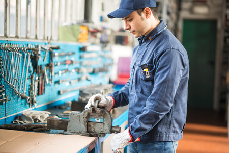 Worker securing a metal plate in a vise Stock Photo