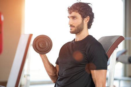 weight lifter: Man working out in a gym. Bright lens flare