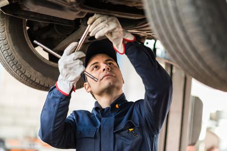 budget repair: Portrait of a mechanic repairing a lifted car