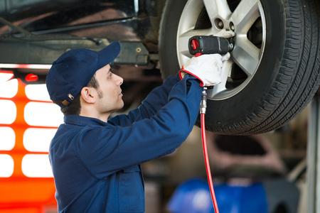 mechanician: Mechanician changing car wheel in auto repair shop Stock Photo