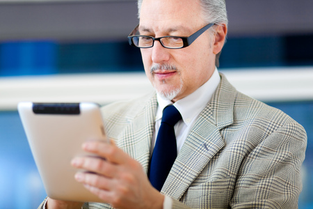 Senior businessman using his tablet photo