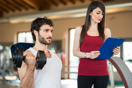 Man working out in a gym while his personal trainer looks at the execution Stock Photo