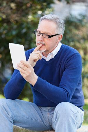 Smiling man looking at his tablet photo