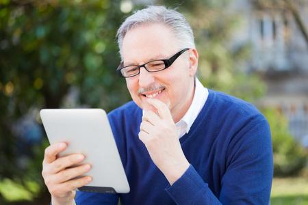 Senior man using a digital tablet photo