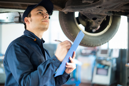 Portrait of a mechanic taking notes while inspecting a car photo