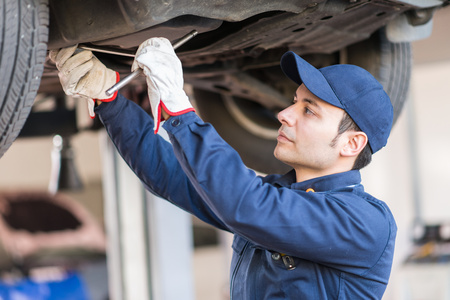 Portrait of a mechanic fixing a car in his garage photo