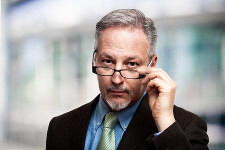 Portrait d'un homme d'affaires mûr tenant ses lunettes de vue Banque d'images - 77110058