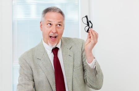 Businessman holding glassesand having an idea Stock Photo