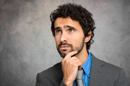 Pensive businessman against a grungy background