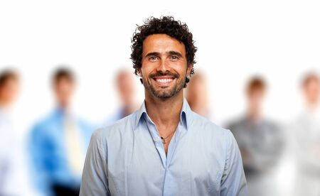 Portrait of a young smiling man in front of a group of people