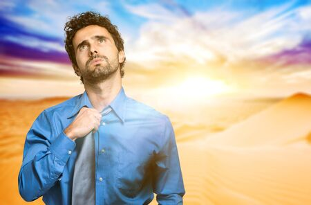 Fired businessman sweating in the desert Stock Photo