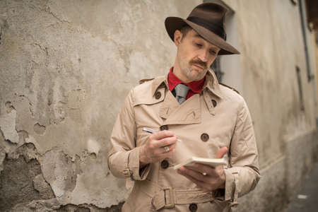 Detective writing on a notebook while stadning near an old wall
