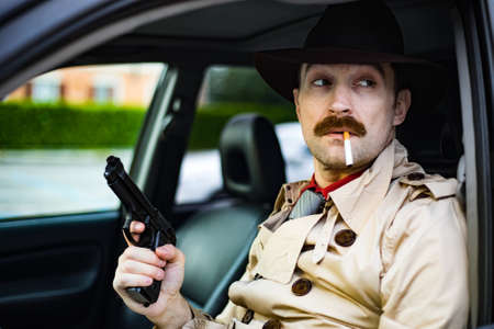 Detective readying his gun while waiting in his car Stock Photo