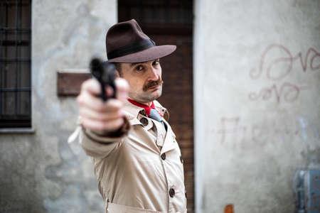 Hitman pointing the gun to the camera, execution concept