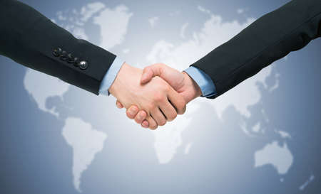 Business people handshake in front of a world map. Blue toned Stock Photo