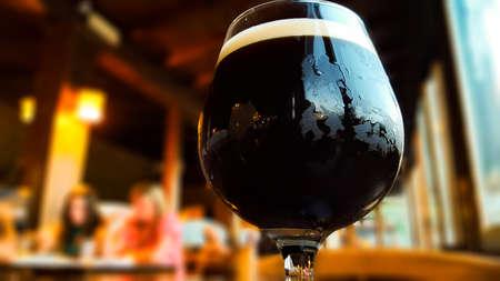 Glass of fresh dark beer on rustic pub background