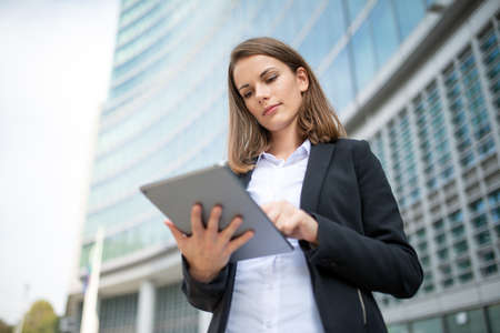 Portrait of a young woman using a tablet out of her office Imagens