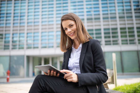 Smiling businesswoman using a digital tablet outdoor sitting on a bench