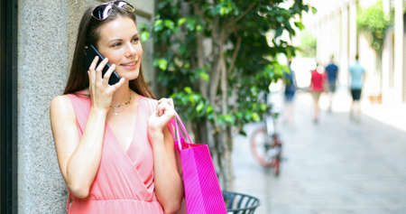 Young woman talking on the phone while shopping in a city