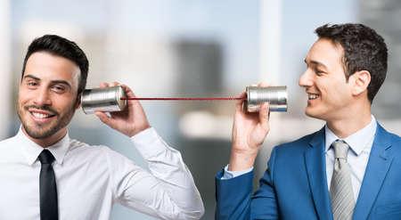 Men talking on tin can phone Foto de archivo