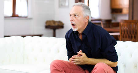 Senor guy watching sports on tv and shouting