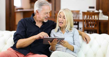 Portrait of a smiling mature couple using digital tablet on sofa at home Foto de archivo