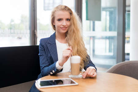 Young businesswoman on a coffee break. Using tablet computer. 免版税图像