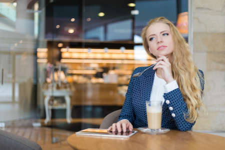 Young businesswoman on a coffee break. Using tablet computer. 免版税图像 - 154905749
