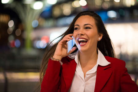 Cheerful woman talking on her mobile phone at night