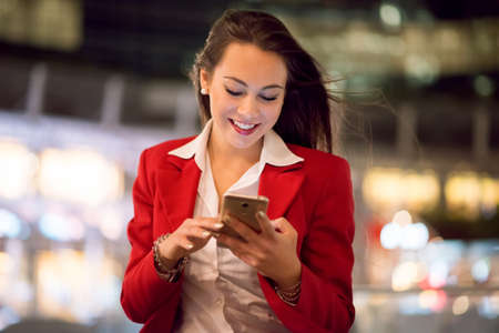 Business woman using her cell phone at night outdoors in a big city