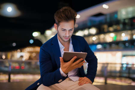 Portrait of man using his tablet in a city at night