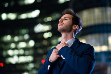 Businessman adjusting his necktie at night 免版税图像