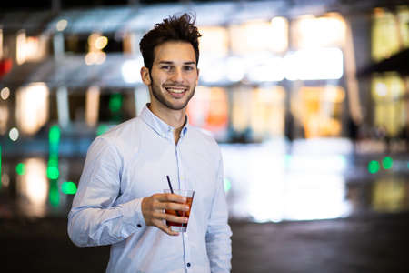 Young man holding a drink at a night club outdoor 免版税图像 - 154905971
